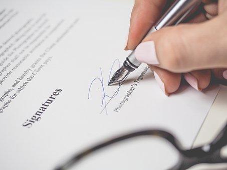 Frau unterschreibt mit Füller